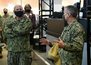 Chief of Naval Operations (CNO) Adm. Mike Gilday receives a brief from Commander Naval Information Forces, Vice Adm. Brian Brown while touring the Naval Network Warfare Command (NNWC) and Navy Cyber Defense Operations Command (NCDOC) watch floor. (U.S. Navy photo by Robert Fluegel/RELEASED)