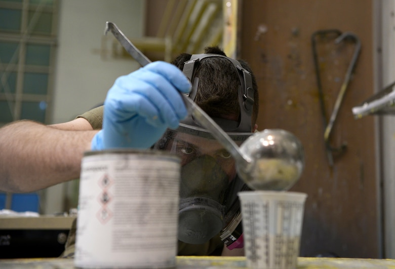 U.S. Air Force Airman Mason Henry, a 354th Maintenance Squadron Aircraft Structural Maintenance journeyman, mixes paint for an F-16 Fighting Falcon part on Eielson Air Force Base, Alaska, Oct. 8, 2020.