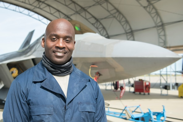 A man wearing blue coveralls smiles for a portrait in front of a jet