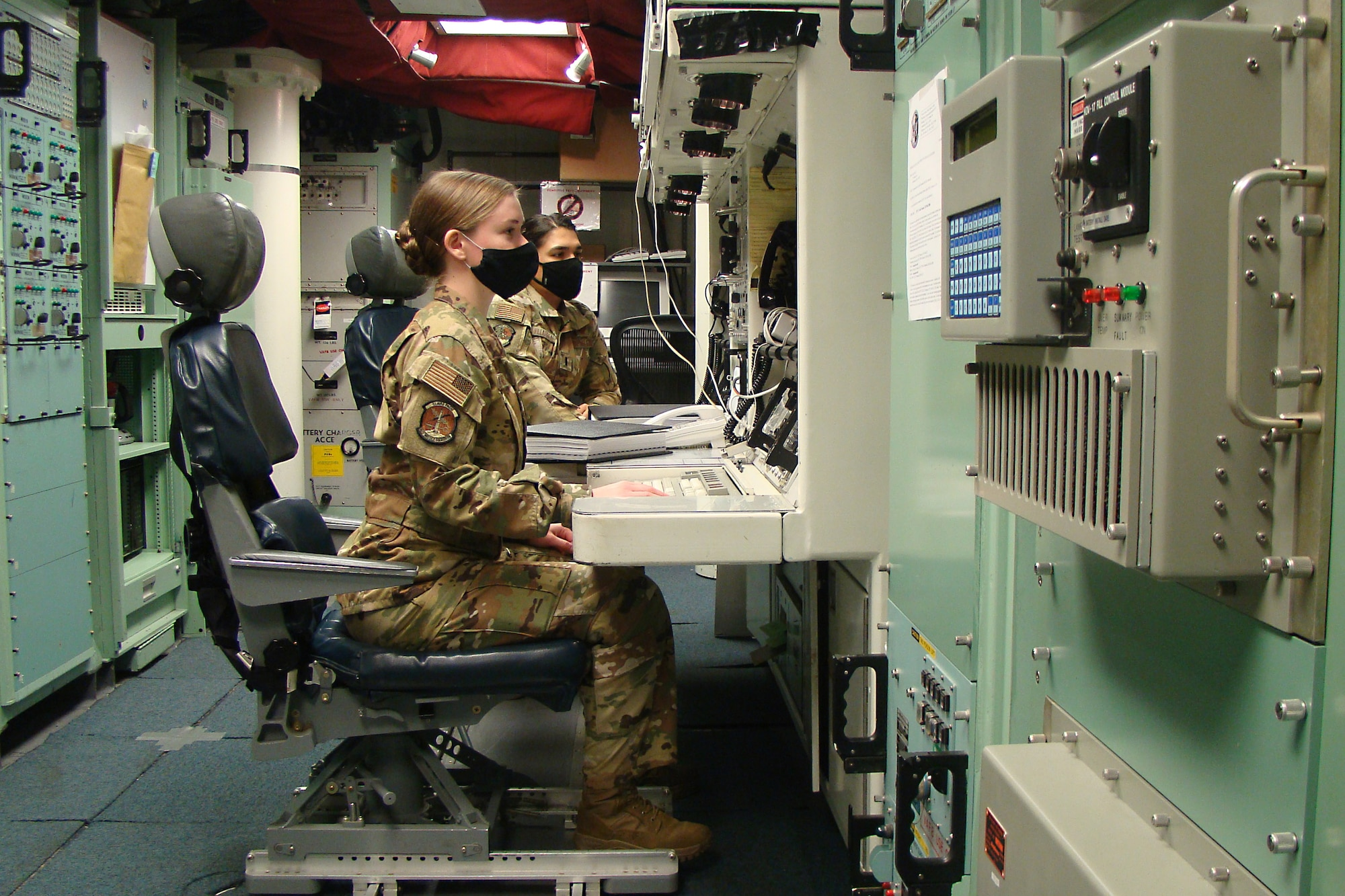 Missileers sit in a launch control center.