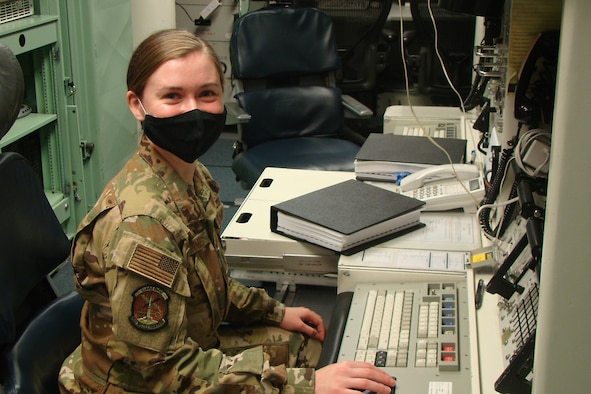 Woman poses for a photo in a launch control center.