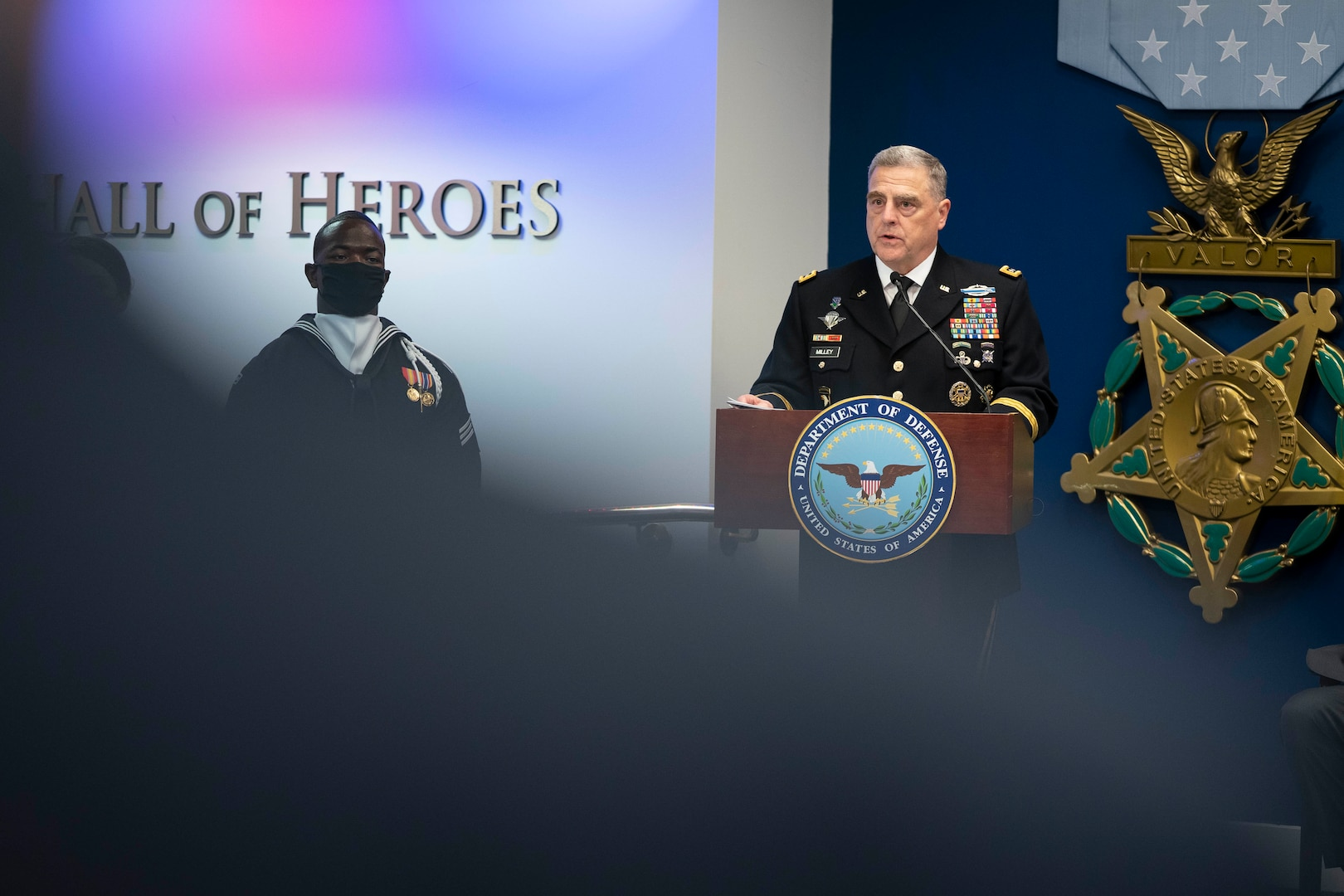 A man in a military uniform stands at a podium.
