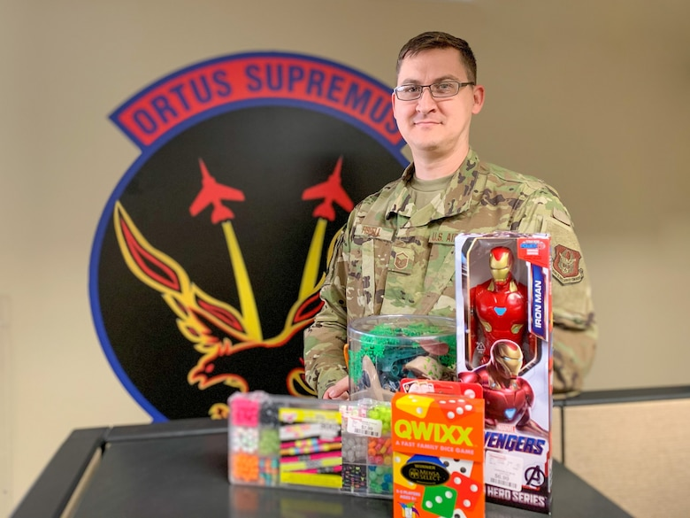 Master Sgt. Caleb Fishell, 926th Aircraft Maintenance Squadron's unit training manager, poses with toys he plans to donate to a local nonprofit, Oct. 29, at Nellis Air Force Base, Nev. Fishell has been giving back to local Las Vegas families since 2012.