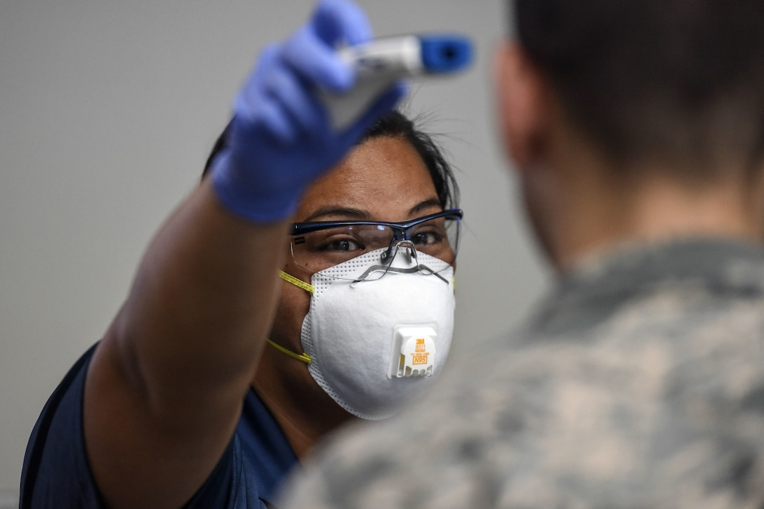 Kuhina Talimalie, 735th Air Mobility Squadron passenger service and baggage agent, uses a no-touch thermometer to check a service member's temperature at Joint Base Pearl Harbor-Hickam, Hawaii, March 25, 2020. Passenger terminal airmen are screening passengers for fever to help mitigate the spread of COVID-19.