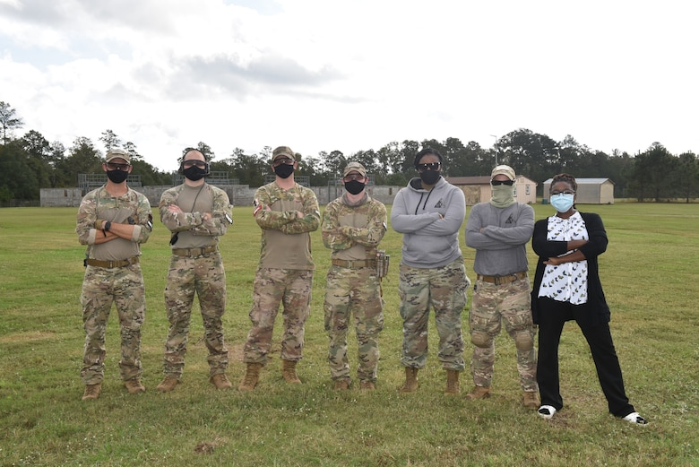 Photo shows group of people standing with arms crossed.
