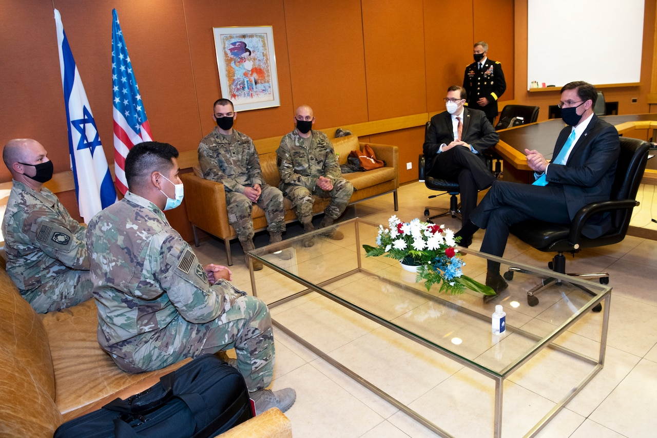 Soldiers sit around a coffee table with Defense Department leaders.