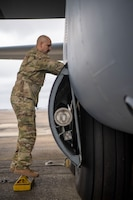 A loadmaster conducts a pre-flight check on a C-130J Super Hercules.