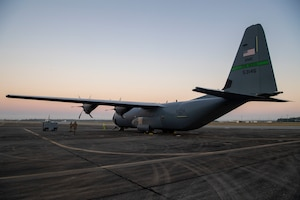 A C-130J sits on the runway at sunrise.
