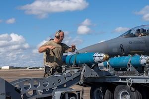 An Airman moves a training munition onto a jammer.