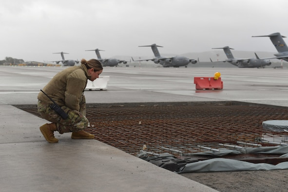 An Airman kneeling beside a construction site on an airfield.