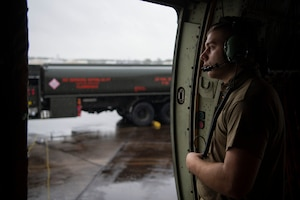 An Airman looks out the side of a C-130J.