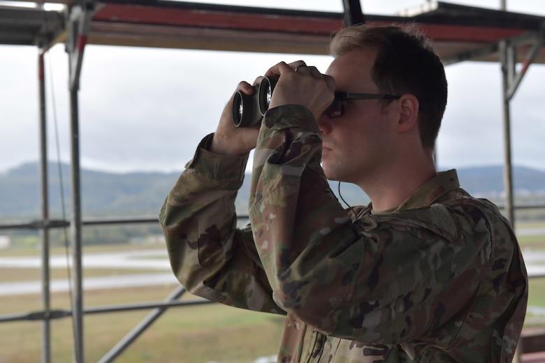 An Airman looks through binoculars.