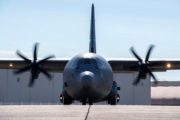 A C-130J sits on a runway.