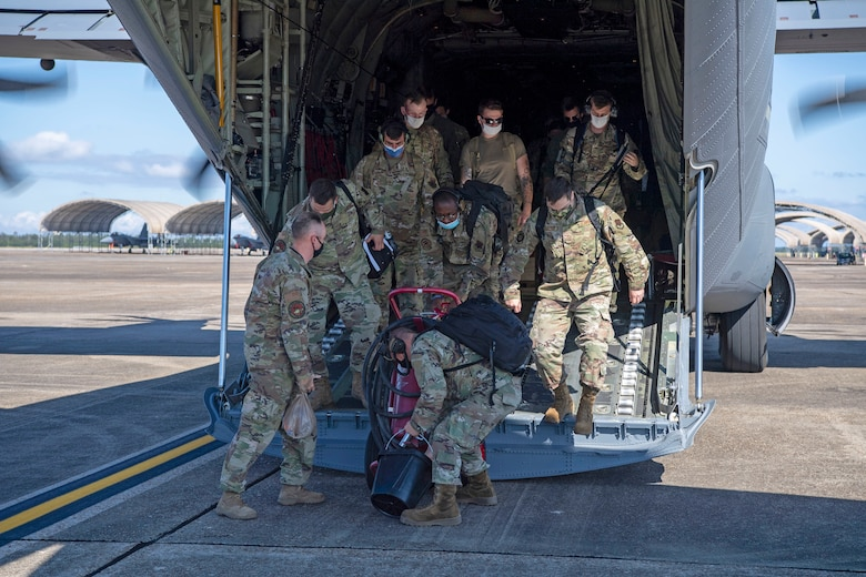 Airmen unload a fire bottle out the back of a C-130J Super Hercules.