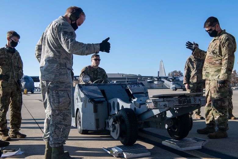 Airmen weigh a jammer before loading it onto a C-130J.