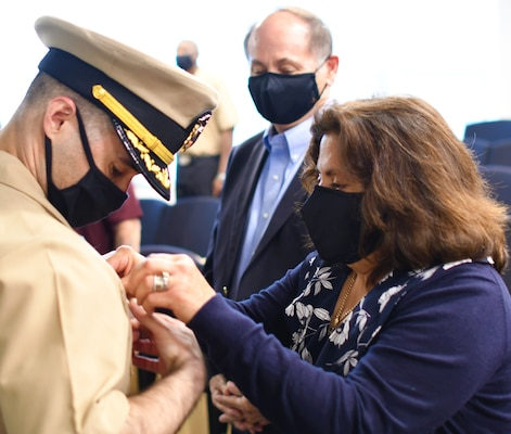 """IMAGE: VIRGINIA BEACH, Va. (Oct. 16, 2020) – Cmdr. Michael Aiena, commanding officer of Naval Surface Warfare Center Dahlgren Division (NSWCDD) Dam Neck Activity, receives his command ashore pin from his mother while his father looks on at a change of command ceremony held at Dam Neck Activity's Hopper Hall auditorium. Aiena relieved Cmdr. Joe Oravec during the ceremony. """"My parents are the reason I'm here,"""" said Aiena, who told the audience on site and over a live Teams broadcast that he is humbled to assume command at NSWCDD Dam Neck Activity. """"I am thrilled with this opportunity to work with the Sailors and civilians that make up the command for they are our most valuable resource.""""  (U.S. Navy photo/Released)"""
