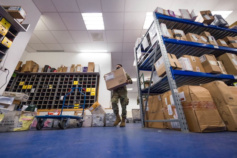 U.S. Air Force Airman Adrian Farias, 786th Force Support Squadron military postal clerk, carries a package to a customer at the Northside Post Office at Ramstein Air Base, Germany, Oct. 28, 2020. The post office utilizes a digital inventory system that allows postal clerks to quickly identify the location of a package. (U.S. Air Force photo by Senior Airman Noah Coger)
