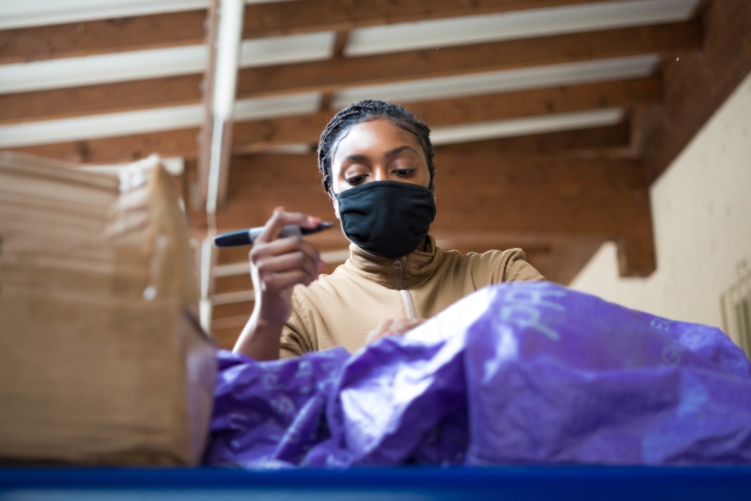 U.S. Air Force Senior Airman Barlitra Dirance, 786th Force Support Squadron military postal clerk, receives parcels at Ramstein Air Base, Germany, Oct. 28, 2020. The Northside Post Office utilizes a stationary conveyor belt, capable of extending into a semi-trailer to expedite processing of incoming packages. (U.S. Air Force photo by Senior Airman Noah Coger)
