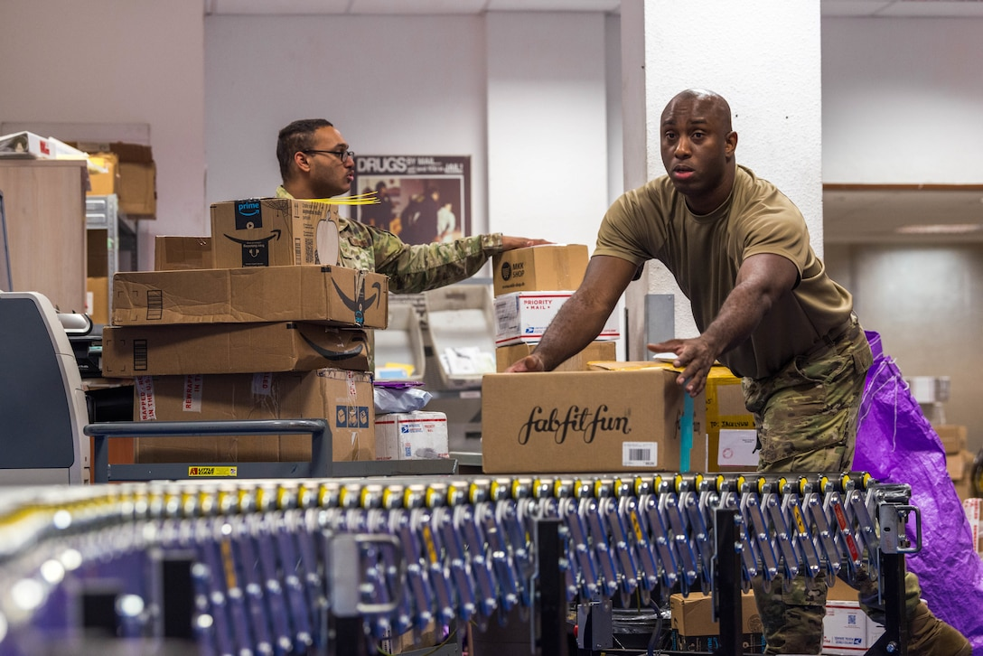 U.S. Air Force Staff Sgt. Kamar Francis, 786th Force Support Squadron postal service center noncommissioned officer in charge, grabs a package off of a roll-out conveyor belt at Ramstein Air Base, Germany, Oct. 27, 2020. Two roll-out conveyor belts that extend to both sides of the Northside Post Office are used in conjunction with a stationary conveyor belt to accelerate processing incoming packages. (U.S. Air Force photo by Senior Airman Noah Coger)