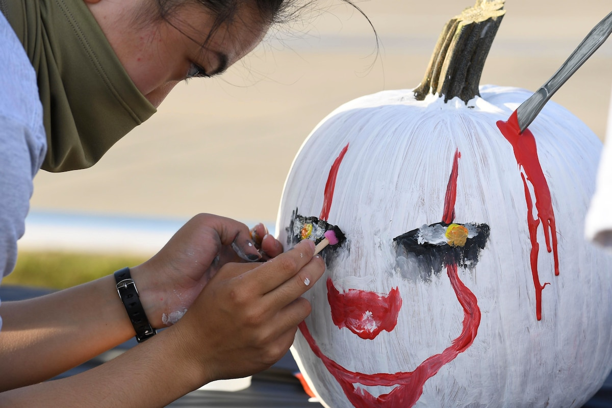 An airman wearing a face mask paints a pumpkin.