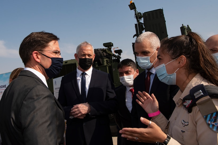 An Israeli military officer speaks to a group of people in suits wearing protective face masks.