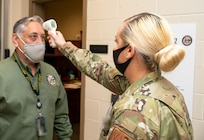 CAMP ATTERBURY, IND. (OCT. 10, 2020) Joseph Chacon, Joint Staff Bold Quest Operations Director, has his temperature checked by Technical Sergeant Alexandria Harville, an aerospace medical technician assigned to the Virginia Air National Guard 192nd Medical Group  during capability demonstration Bold Quest 20.2. Members of the 192nd Medical Group helped develop the medical standard operating procedures for Bold Quest participants to prevent and respond to any COVID-19 outbreak. (U.S. Navy photo by Mass Communication Specialist 2nd Class Jonathan Word)