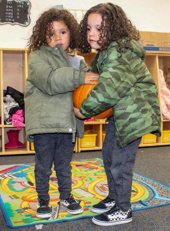 Phoenix, 3, left, and Axton, 5, carry a pumpkin during the 50th Force Support Squadron's pumpkin patch event at the Child Development Center Oct. 23, 2020, at Schriever Air Force Base, Colorado. The CDC held the pumpkin patch indoors to accommodate for inclement weather. The children selected a pumpkin to take home and decorate. (U.S. Space Force photo by Marcus Hill)