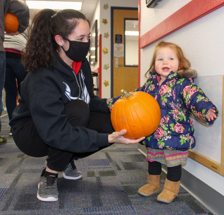 Staff Sgt. Megan Aycock, Colorado Springs Regional Command Post emergency actions controller, left, hands a pumpkin to her daughter Mabry, 1, as they prepare to leave the Child Development Center at Schriever Air Force Base Oct. 23, 2020. Parents picked up pumpkins to decorate for fun or to enter into the 50th Force Support Squadron's pumpkin carving contest. (U.S. Space Force photo by Marcus Hill)