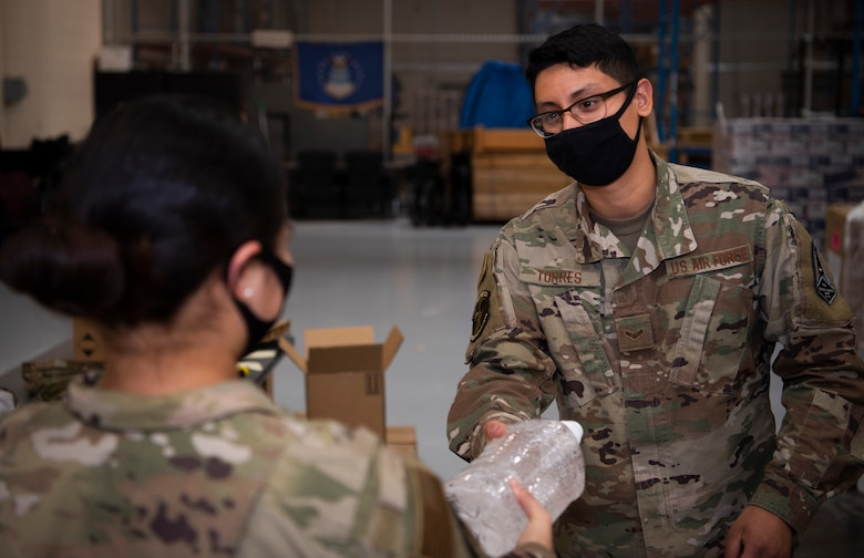 Airman 1st Class Juan Torres, 50th Contracting Squadron contract specialist, gives hand sanitizer to an Airman Oct. 29, 2020, at Schriever Air Force Base, Colorado. The 50th CONS provided hand sanitizer to 20 units who requested the product to battle COVID-19. (U.S. Space Force photo by Airman 1st Class Jonathan Whitely)