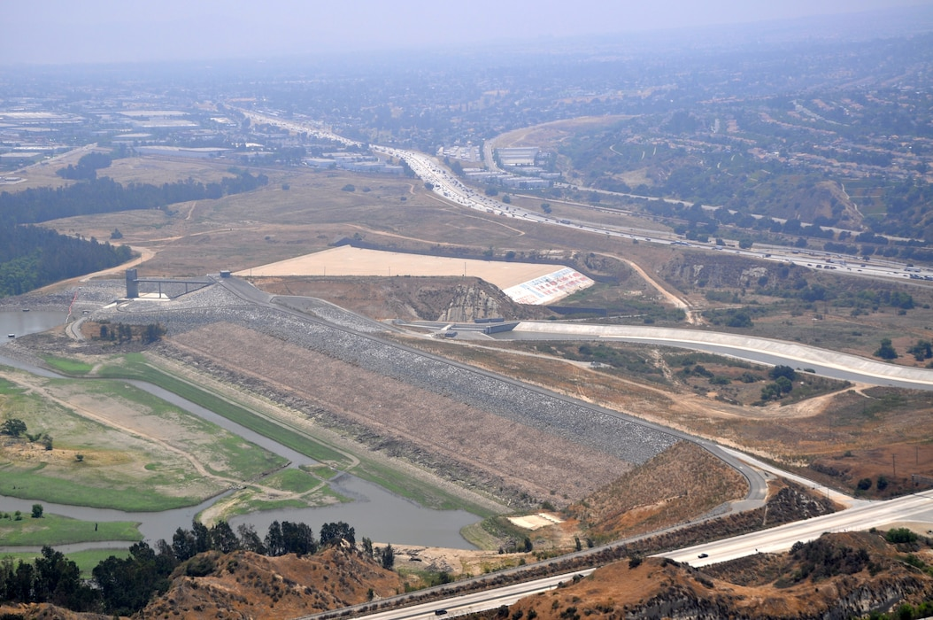 Prado Dam, located in Corona, California, can be seen from a helicopter in this undated aerial photo. The U.S. Army Corps of Engineers Los Angeles District and the Orange County Flood Control District recently signed an amendment to use Bipartisan Budget Act of 2018 funds for select features of the Santa Ana River Mainstem project, which include raising the Prado Dam spillway by 20 feet; completing the lower Norco Bluffs toe protection project, and the Alcoa Phase 2 and River Road dikes; and ongoing mitigation responsibilities associated with the Prado Dam project features.