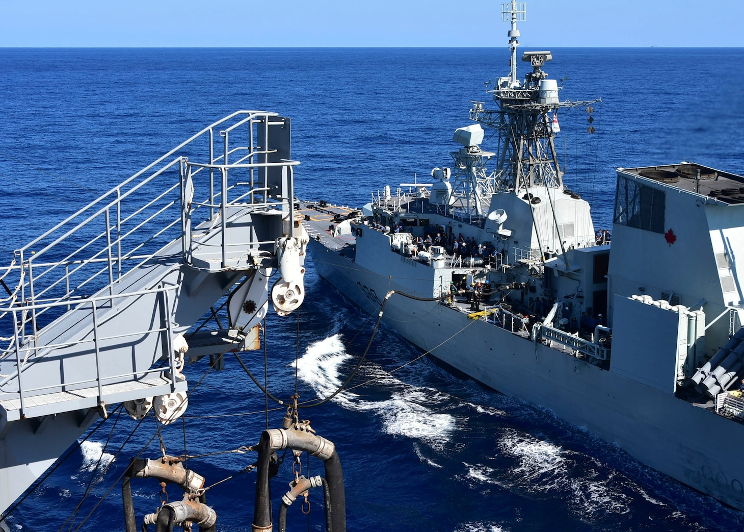 PHILIPPINE SEA (Oct. 25, 2020) – The U.S. Navy Military Sealift Command Henry J. Kaiser-class fleet replenishment oiler USNS Tippecanoe (T-AO 199), left, refuels the Royal Canadian Navy Halifax-class frigate HMCS Winnipeg (FFH 338) during an underway replenishment prior to participating in Keen Sword. Keen Sword is a joint, bilateral, biennial field-training exercise involving U.S. military and Japan Self-Defense Force personnel, designed to increase combat readiness and interoperability of the Japan-U.S. alliance. (US. Navy photo by Christopher Bosch)