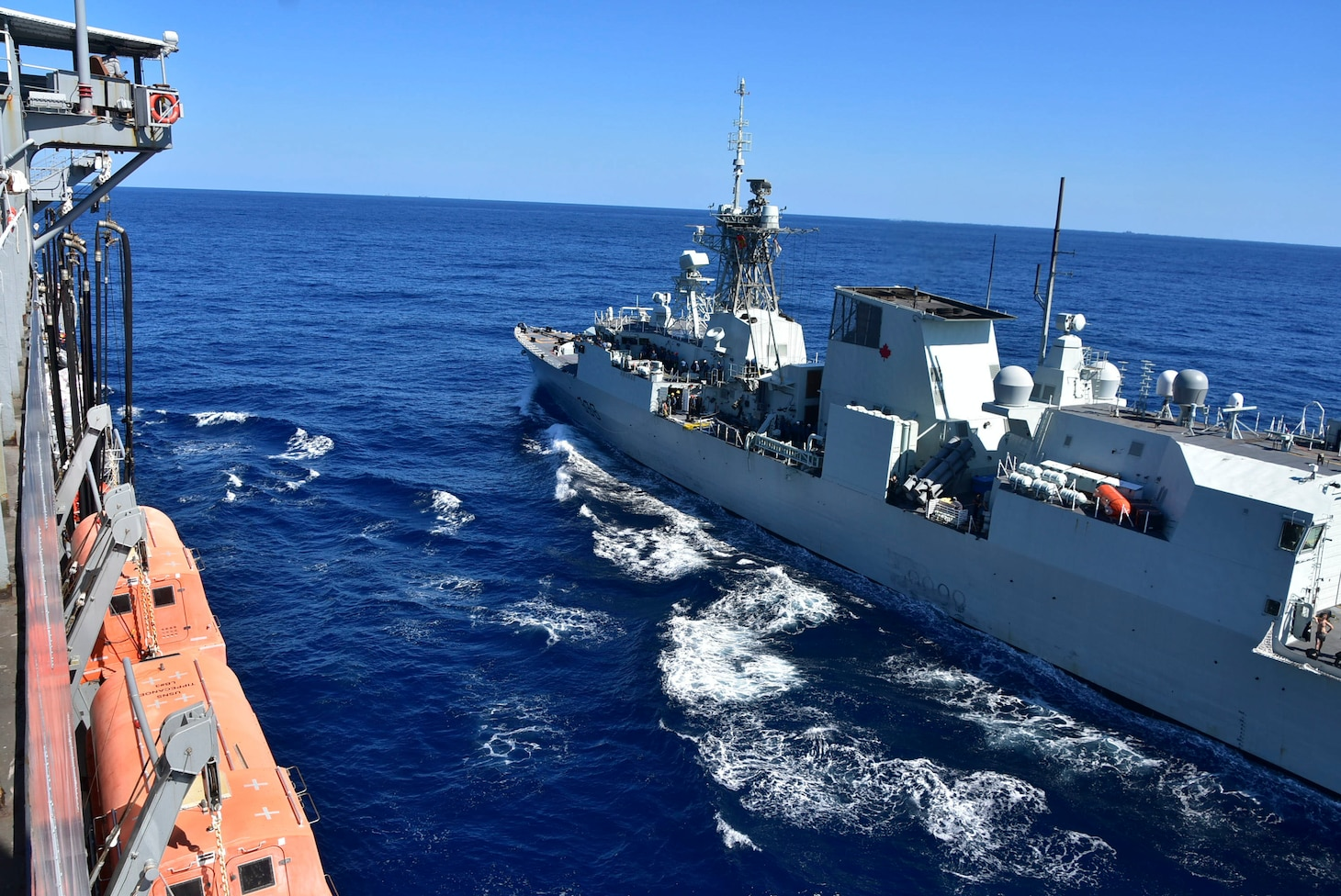 PHILIPPINE SEA (Oct. 25, 2020) – The U.S. Navy Military Sealift Command Henry J. Kaiser-class fleet replenishment oiler USNS Tippecanoe (T-AO 199), left, steams alongside the Royal Canadian Navy Halifax-class frigate HMCS Winnipeg (FFH 338) during an underway replenishment prior to participating in Keen Sword. Keen Sword is a joint, bilateral, biennial field-training exercise involving U.S. military and Japan Self-Defense Force personnel, designed to increase combat readiness and interoperability of the Japan-U.S. alliance. (US. Navy photo by Christopher Bosch)