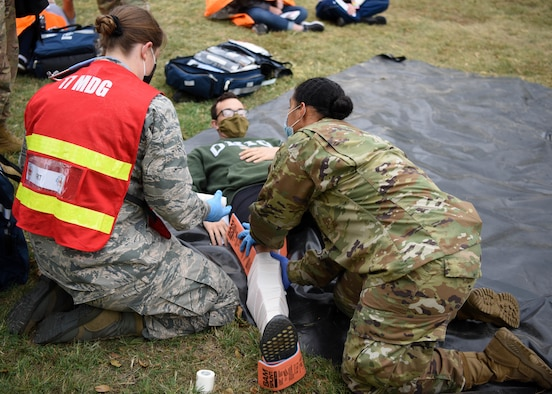 17th Medical Group medics put a splint on a patient during a Ready Eagle exercise on Goodfellow Air Force Base, Texas, Oct. 23, 2020. The medics responded to a simulated explosion and performed first-aid on volunteer casualties. (U.S. Air Force photo by Airman 1st Class Ethan Sherwood)