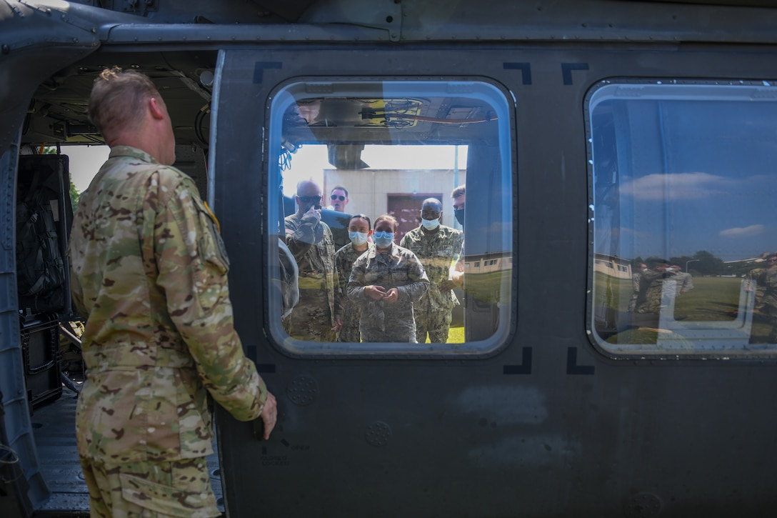 Medics listen to a safety brief concerning loading and unloading wounded patients into a UH-60 helicopter.