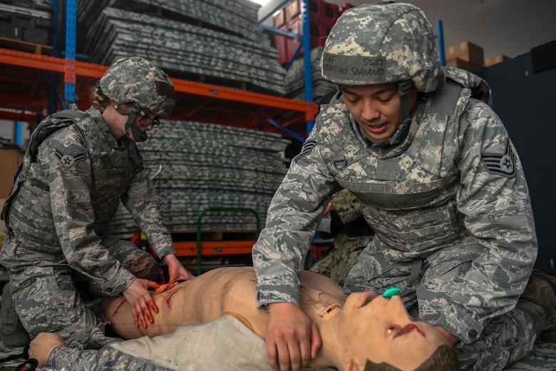 Medics interact with a wounded training mannequin during the Tactical Field Care phase of the Tactical Combat Casualty Care.