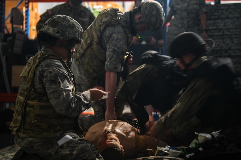 Air Force and Navy medical personnel interact with a wounded training mannequin.