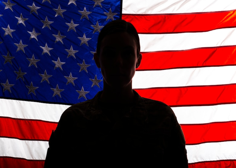 a silhouette of Senior Airman Zoe Wockenfuss stands in front of an illuminated American flag