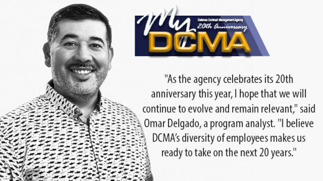 Smiling man standing against the wall with a My DCMA 20th anniversary logo on the photo