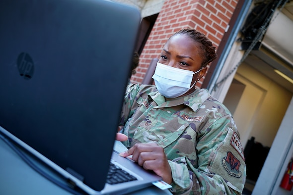 A female medical technician wears a protective face mask as she sits behind a grey laptop.