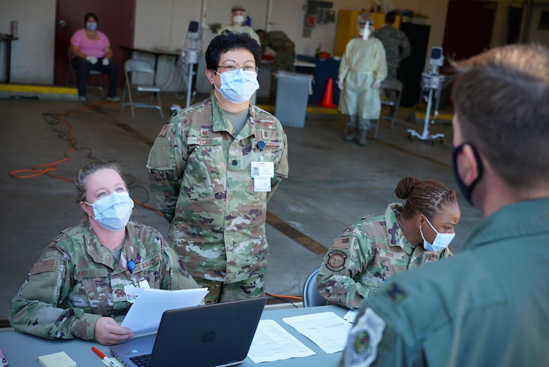 Two women in military uniform and face masks look at a patient as he checks in for an appointment.