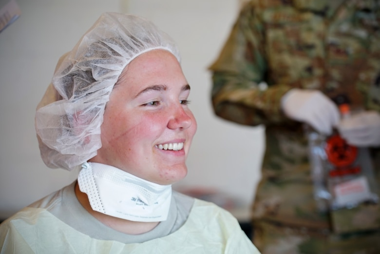 Portrait of a woman in personal protective gear smiling.