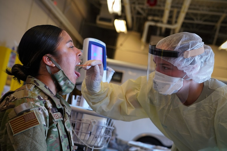 A woman in military uniform opens her mouth and sticks out her tongue as a medical technician wearing gloves, a face mask and protective gown swabs the back of her throat.