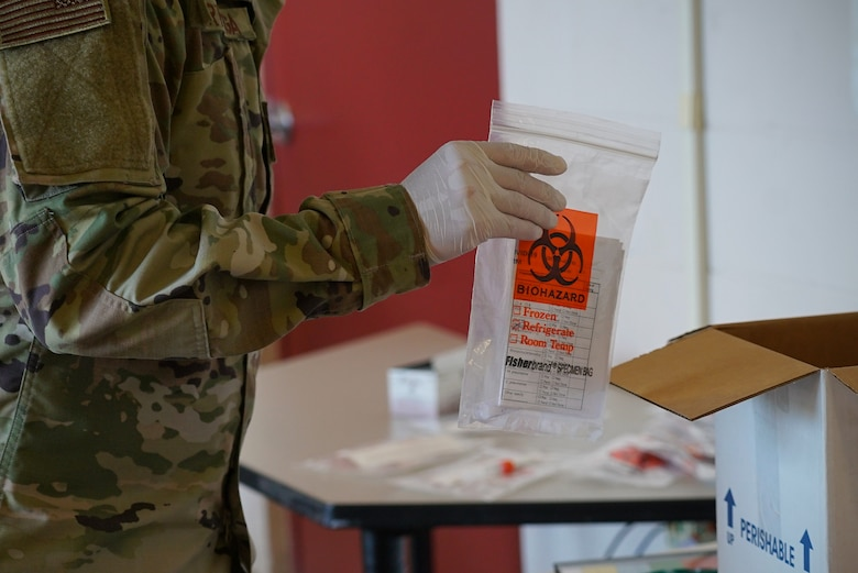 A gloved hand holds a clear and orange biohazard bag near a box to be shipped later.