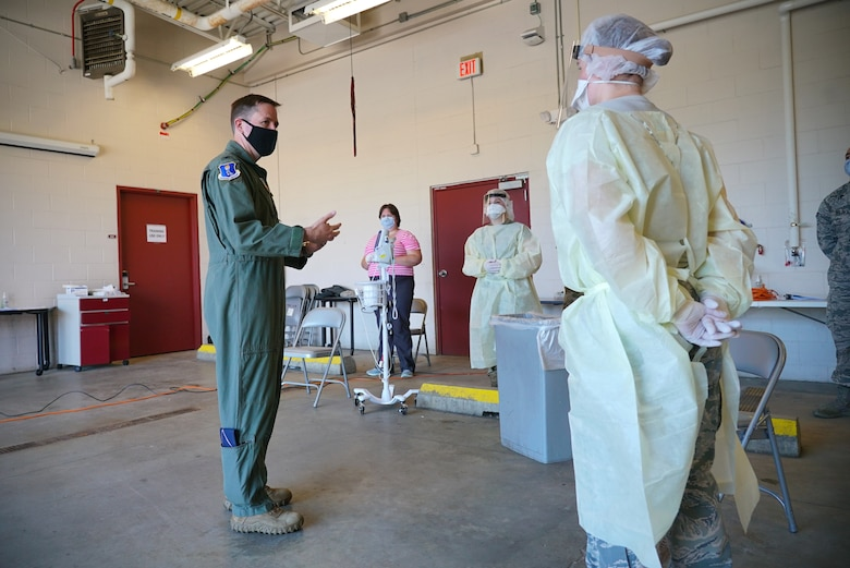 Man in flight suit looks at woman in medical protective gear as he talks.