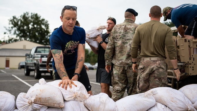 Airmen from the 2nd Security Forces Squadron unload sand bags at Barksdale Air Force Base, La., Aug. 28, 2020. The Airmen were part of a Disaster Response Force organized to help the base recover from damage caused by Hurricane Laura. (U.S. Air Force photo by Airman 1st Class Jacob B. Wrightsman)