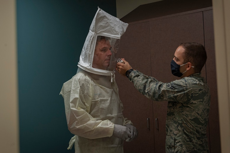 Photo of an Airman spraying solution for a mask fitting