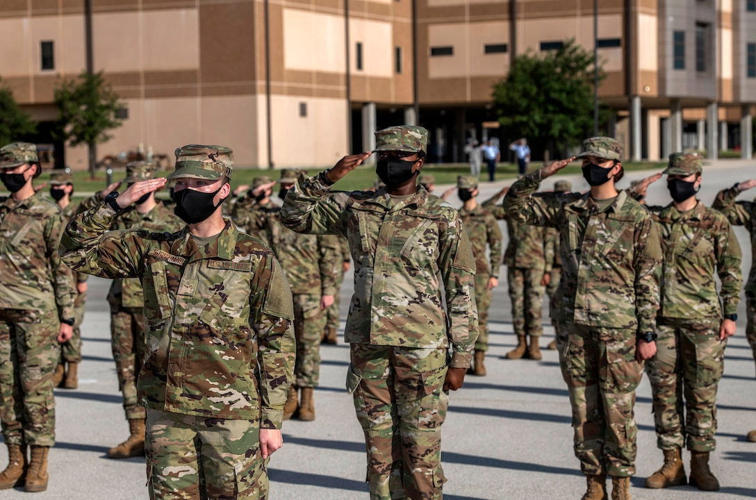 Air Force recruits in uniform and in formation salute.