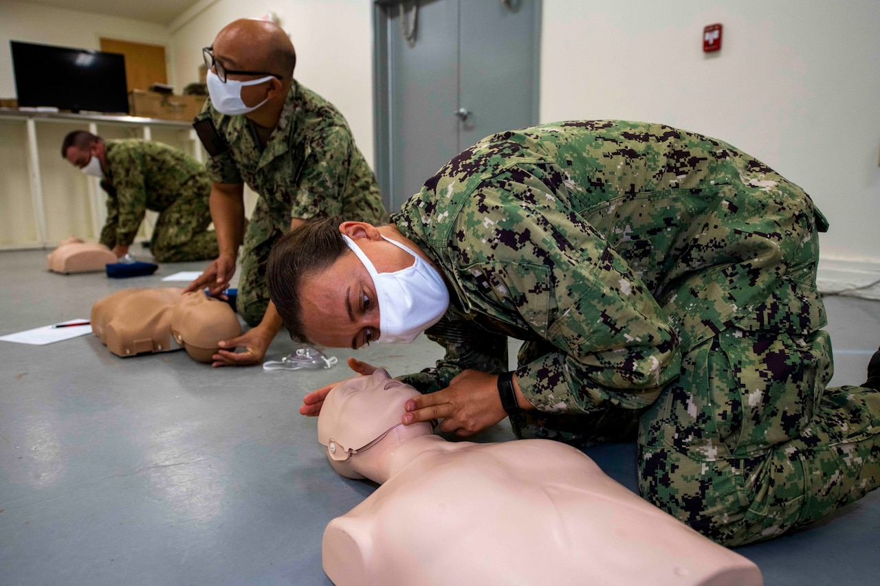 Sailors wearing masks perform CPR on mannequins.