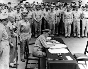 Fleet Admiral Chester W. Nimitz signs the Instrument of Surrender as United States Representative aboard the battleship USS Missouri (BB-63) in Tokyo, Japan,  Sept. 2, 1945.