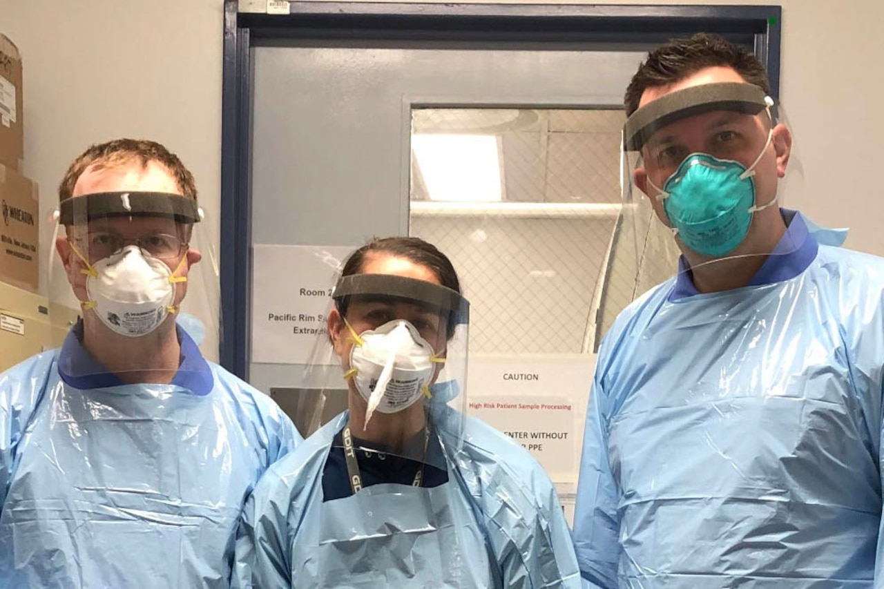 Three people in personal protective equipment stand in a lab doorway.